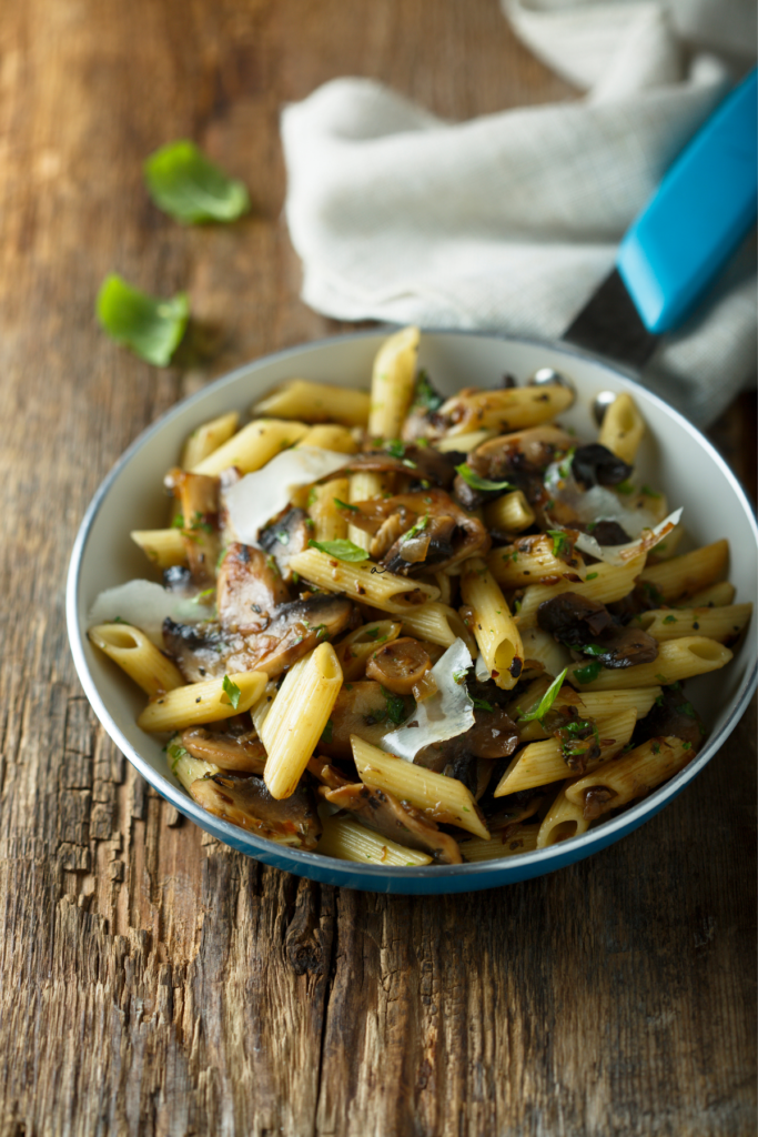 Mushroom pasta in white bowl on natural wooden table- At Your Table